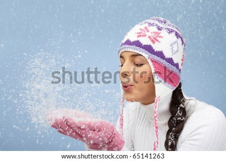 Image of pretty woman in pink gloves and knitted winter cap blowing snow from her palms