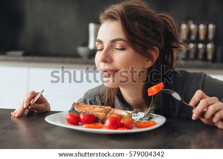 Image of pretty young woman sitting in kitchen while eating and smells fish and tomatoes. Eyes closed.