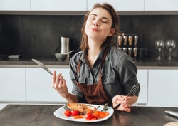 Image of pretty young woman sitting in kitchen while eating fish and tomatoes.