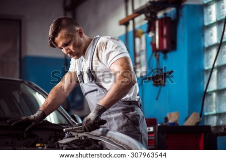 Image of professional uniformed car mechanic working in service station