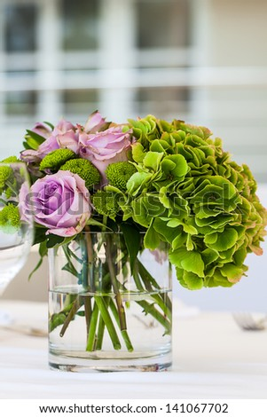 image of purple decaying roses and bright green hydrangeas in a short glass vase as center decoration for a set table #141067702