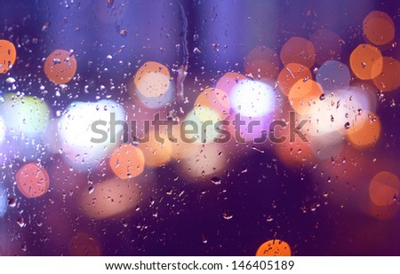 Image of raindrops on window at night in the city