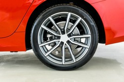 Image of rear side sports car wheel with number and markings on tire sidewall Which indicates the size of the tire ,age, load of the tire