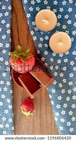 Stock Photo Image of red juicy strawberries and chocolate sweets candles on wooden and textile background in rustic style Tasty delicious natural yummy berry fruit Healthy food with vitamin for diet vegetarian