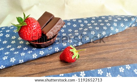 Stock Photo Image of red juicy strawberries and chocolate sweets on the wooden and textile background in rustic style. Tasty delicious natural yummy berry fruit. Healthy food with vitamin for diet and vegetarian