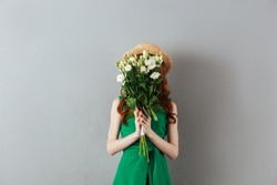 Image of redhead young woman in green dress and hat standing over grey wall background covering face with flowers.