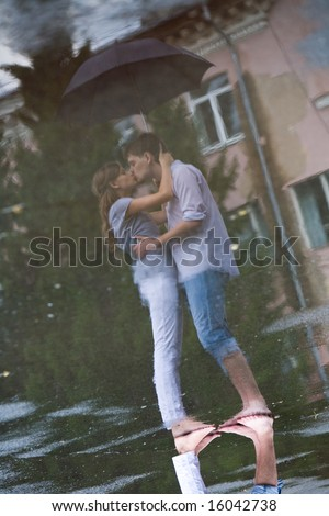 Image of reflection of man and woman kissing  and embracing each other