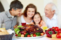 Image of roasted turkey on holiday table and family on background