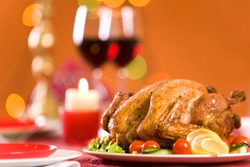 Image of roasted turkey surrounded by vegs on festive table