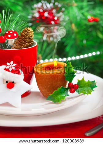 Image of romantic Christmastime dinner with warm candle light, red coffee cup decorated with Santa Claus star and fir cone, beautiful white dinnerware on Christmas tree background, New Year party