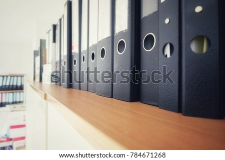 image of row of black view binders on wooden cabinate  for store data paper report in office