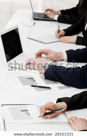 Image of row of people hands writing on papers and typing at briefing
