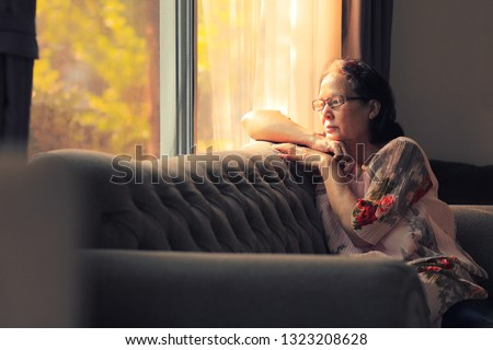 Image of 70s  Asian elderly woman looking outside and flew away ,rim light upon her body.The light and shadow of morning climate background with warm tone.Sad elderly concept.