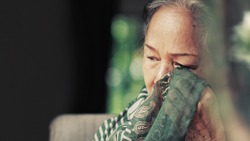 Image of 60s or 70s  Asian elderly woman wiping away her tears  from her eyes with scarf .She may get irritate eye .She looks pain or sick or crying.Sick or sad elderly concept.
