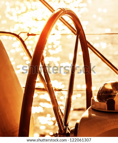 Image of sailboat helm on sunset, steering wheel of yacht, rudder of vessel on sunrise, sea transportation, water transport, active lifestyle, summer vacation, ocean cruise concept - stock photo