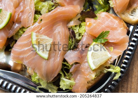 Image of salmon sandwiches with lime on a serving plate