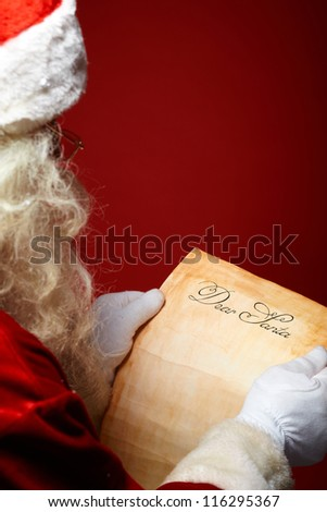Image of Santa Claus reading Christmas letter in his hands
