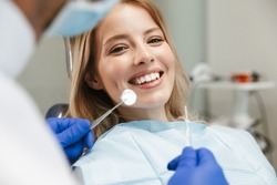 Image of satisfied young woman sitting in dental chair at medical center while professional doctor fixing her teeth
