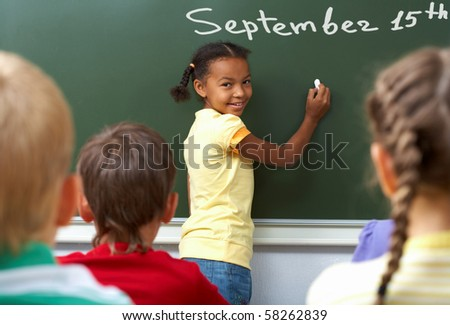 Image of schoolgirl by the blackboard looking at camera through classmates