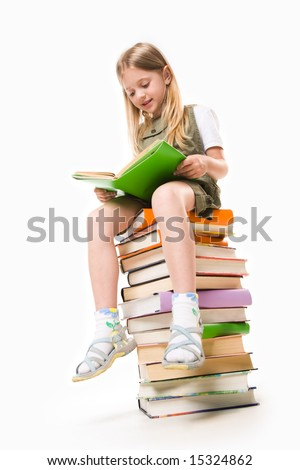 stock photo : Image of schoolgirl sitting on the heap of books and reading one of them