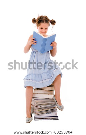 Image of schoolgirl sitting on the heap of books and reading one of them