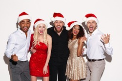 Image of screaming cheerful group of friends wearing christmas hats standing over white isolated background. Looking camera.