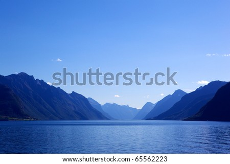 Stock Photo Image of sea and mountains landscape with blue gradient color.