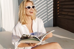 Image of seductive smiling woman in sunglasses reading magazine at hotel on summer beach