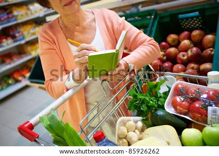 Image of senior woman looking at product list with goods in cart near by
