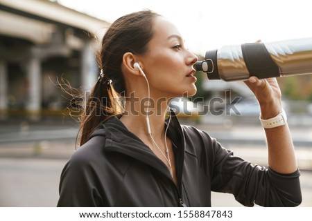 Image of serious athletic woman using earphones and drinking water while working out near road bridge in morning