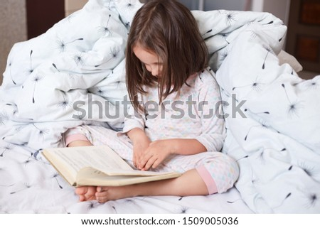 Image of serious preschooler girl reading book in bed, cute kid sitting under blanket with dandelion, darkhaired child reads fairy tale with interest. Early learning and children development concept.
