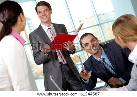 Image of several colleagues interacting at meeting in office