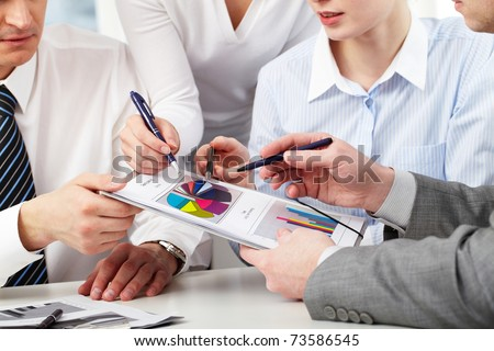 Image of several hands of working partners discussing business charts