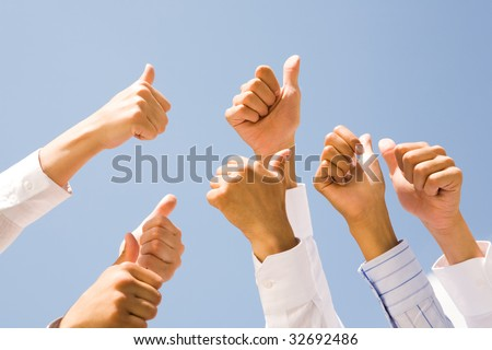 Image of several human hands showing thumbs up against clear blue sky