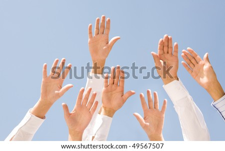 Image of several human palms raised against clear blue sky - stock photo
