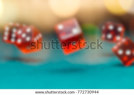 Image of several red dice falling on green table in casino #772730944