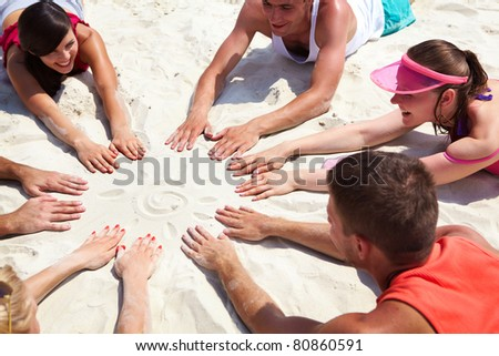 Image of several teens lying on beach and keeping their hands on sand in the form of circle