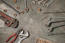 image of several workshop tools on the floor, wrenches, wrenches, pipe wrenches, pliers and bolts