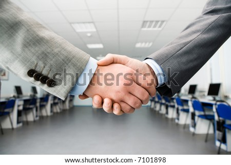 Image of shaking hands making an agreement in the classroom