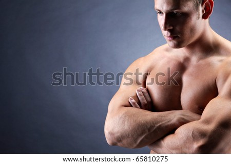 Image of shirtless man with crossed arms over dark background