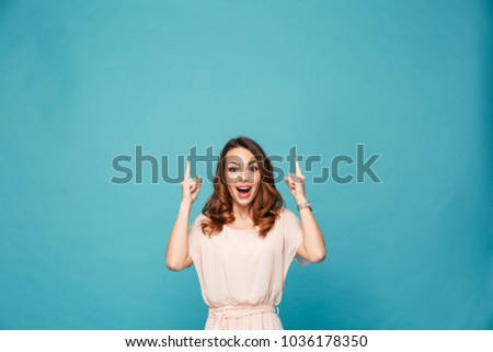 Image of shocked surprised young lady standing isolated over blue background. Looking camera pointing. #1036178350