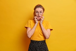 Image of shocked terrified European woman stares at camera with frightened nervous expression grabs face keeps mouth widely opened wears round spectacles t shirt and skirt isolated on yellow wall