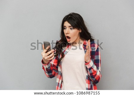 Image of shocked young lady isolated over grey background wall using mobile phone. #1086987155