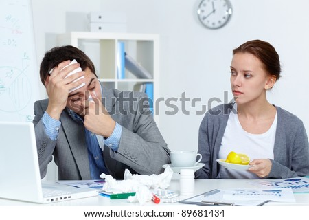 Image of sick businessman and his secretary giving him a cup of tea and lemon in office
