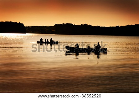 Image of silhouette of canoers on a lake