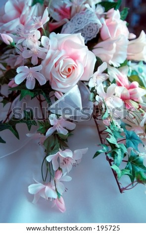 image of silk flower bridal bouquet with green leaves and bow.
