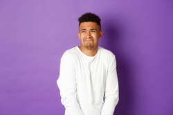 Image of silly guy waiting in line for toilet, grimacing and looking left, need to pee, standing over purple background