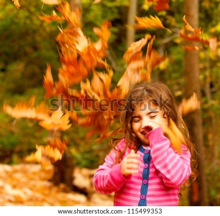 Image of small cute female child enjoying autumn nature, little pretty girl playing game in fall park, beautiful golden trees foliage, nice warm sunny day, carefree childhood