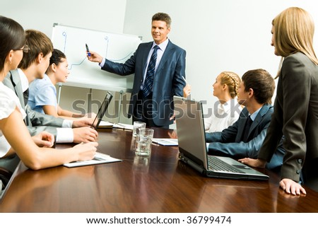 Image of smart business people listening to confident man while he explaining something on whiteboard during seminar