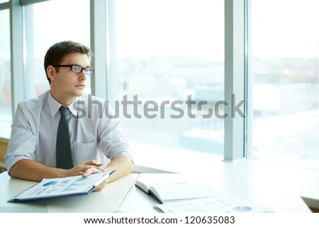 Image of smart businessman with document looking in the office window